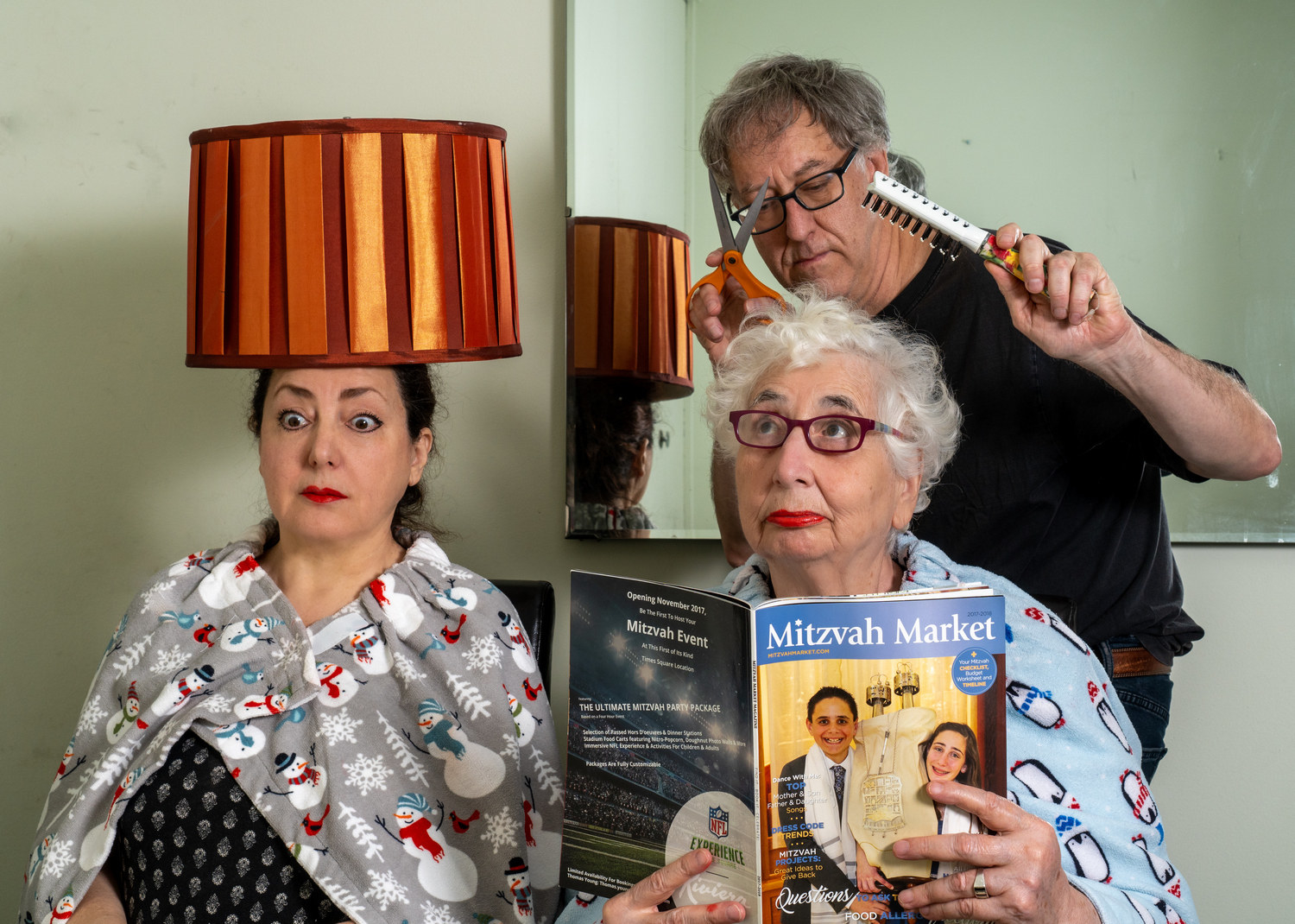 A man play-acting at giving two women a haircut, one with a magazine one with a lampshade