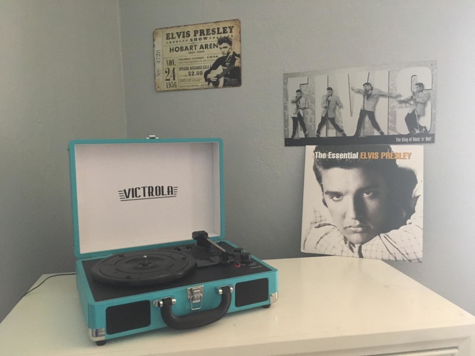Reviewer pic of the rectangle record player that looks like a suitcase in teal, open, showing the black turn table inside
