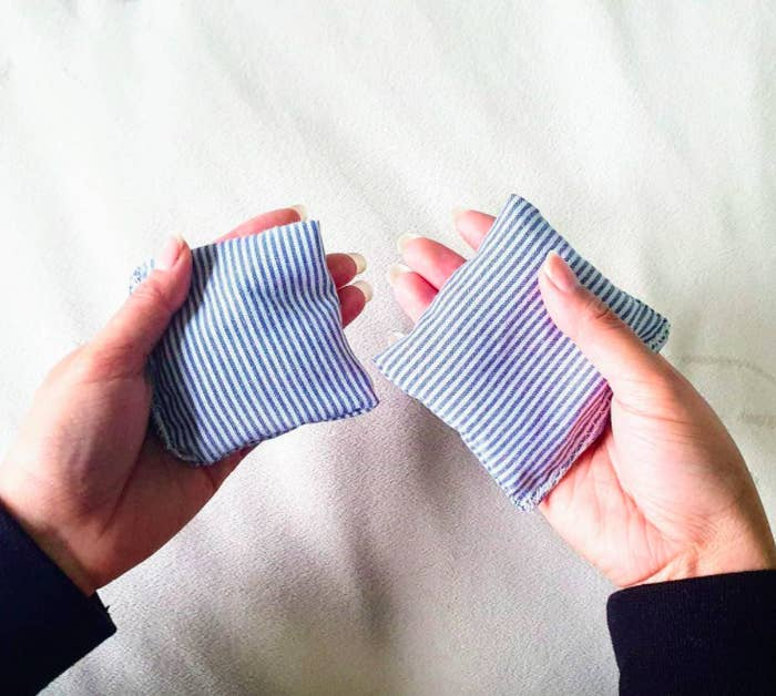 A person holding a hand warmer in each palm
