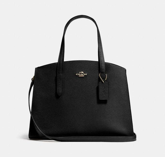 a black carryall bag with gold accents and the coach logo