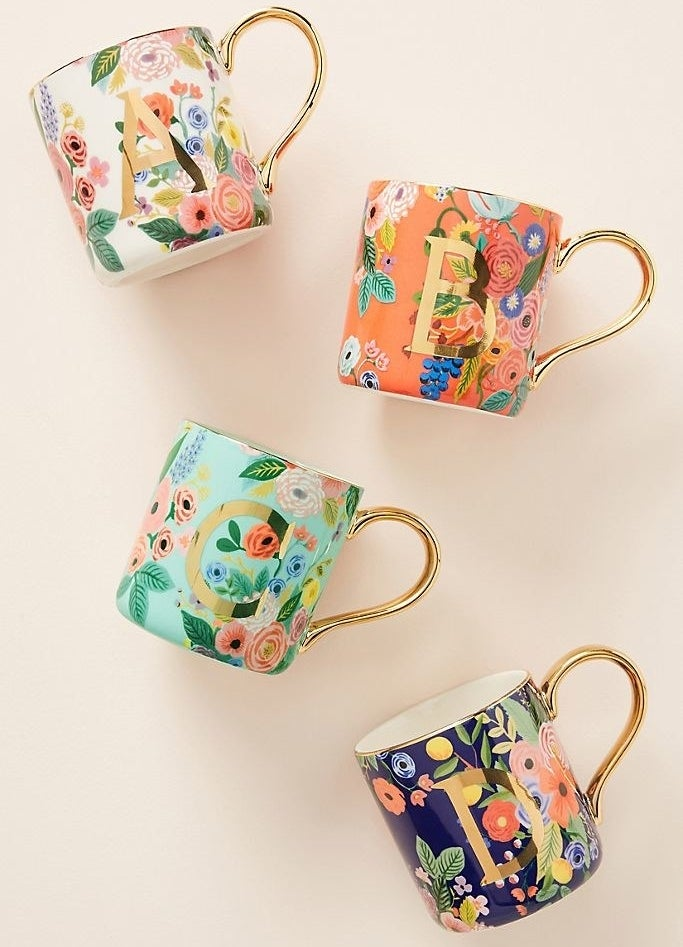 Four mugs with metallic handles and single-letter monogrammes printed with a multicolor floral print
