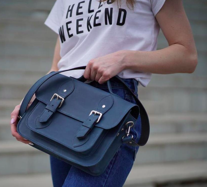 A person holding the satchel against a pair of jeans