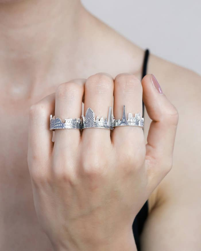 model wearing silver ring with cityscape design