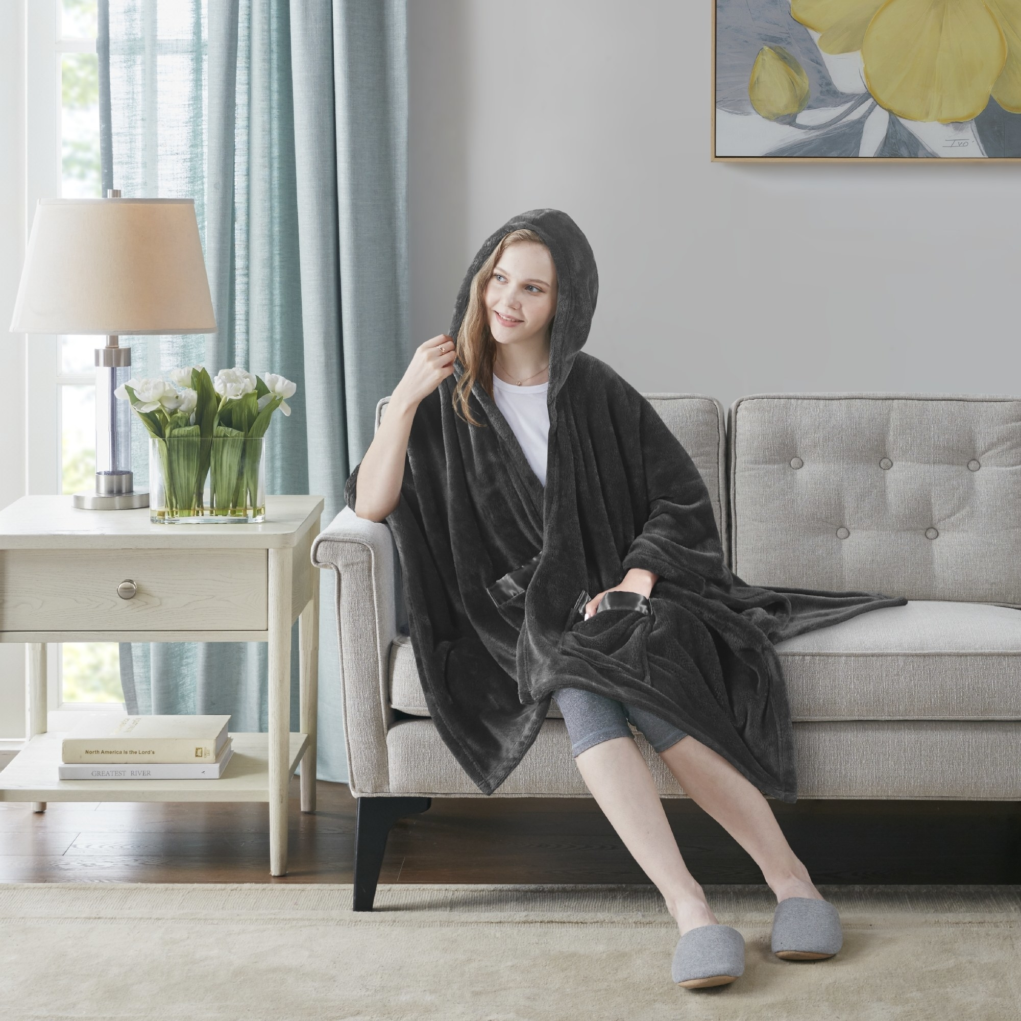 A model wearing the grey wrap on a couch