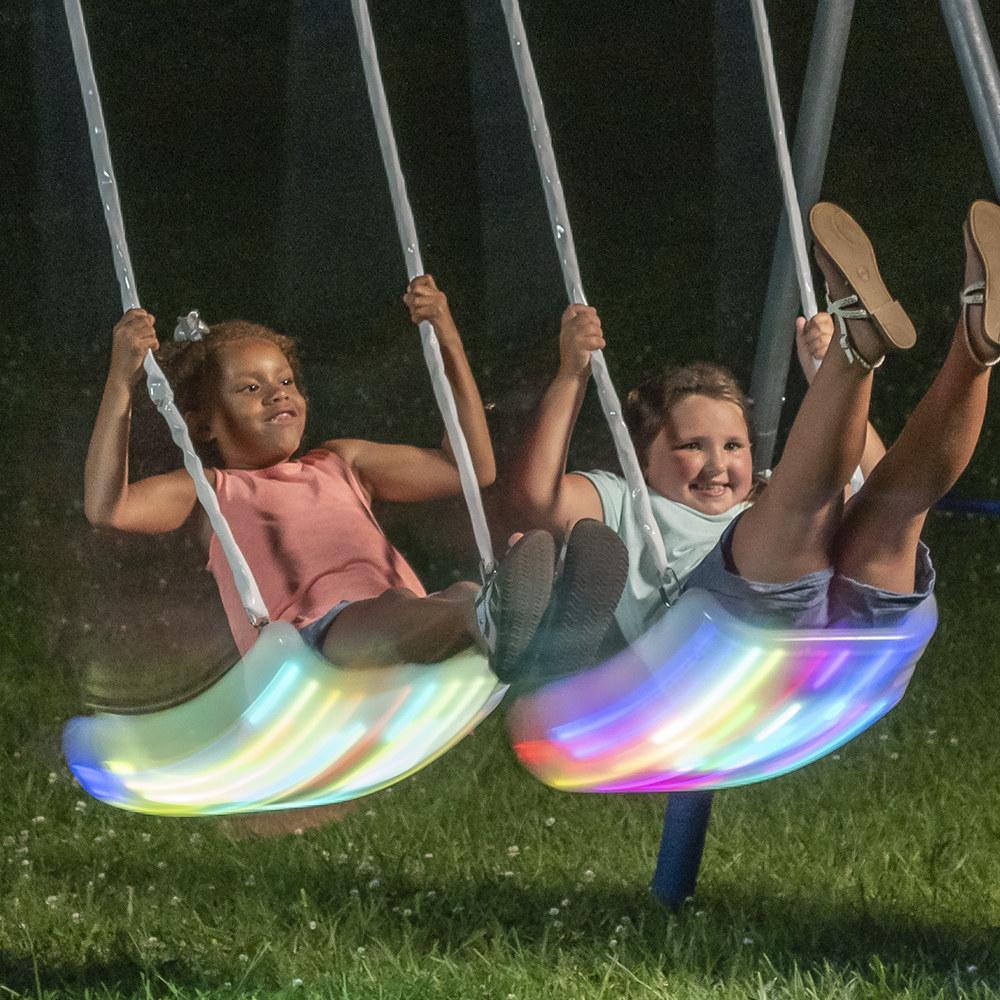 Two children using the lit swings