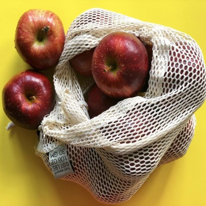 One of the mesh produce bags filled with red apples