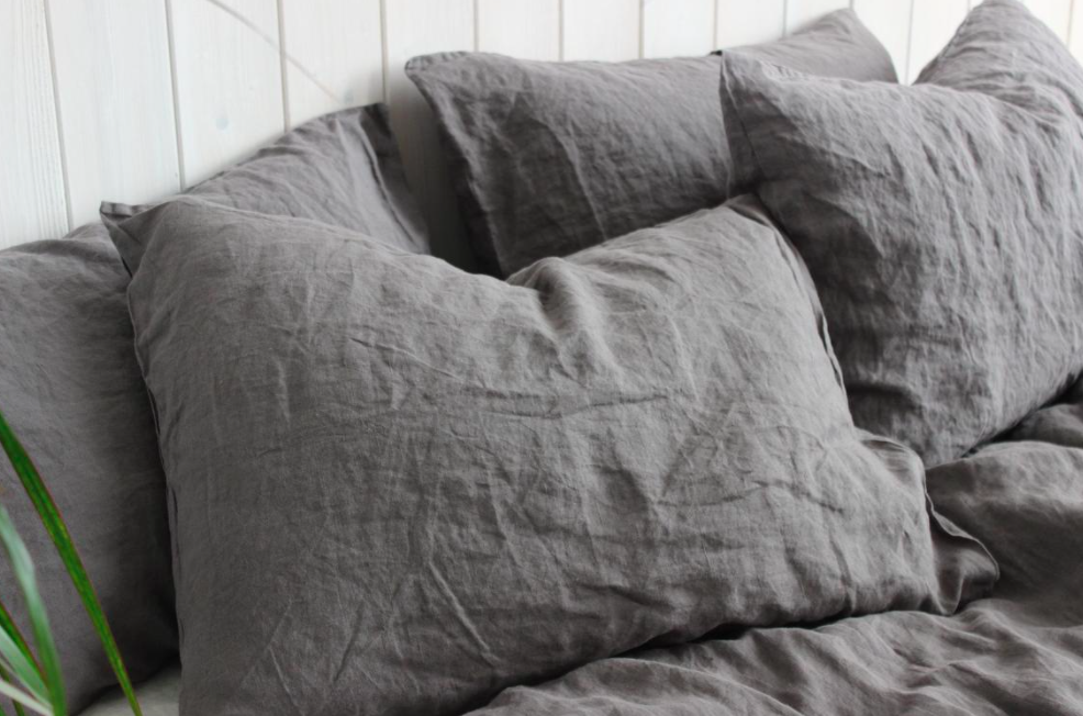 A set of four wrinkled linen pillowcases on a bed