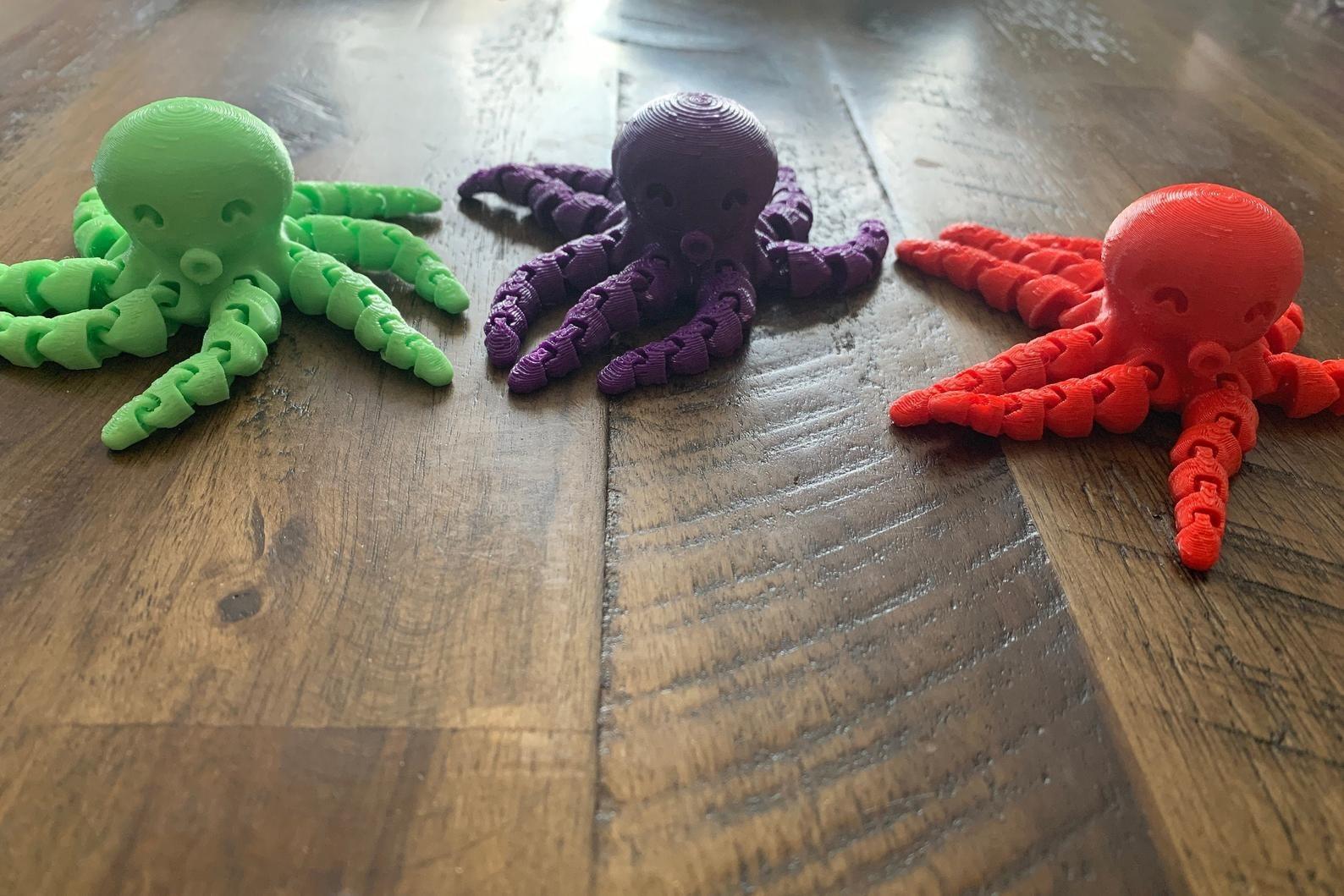 three flexible octopus fidget toys on a wooden surface