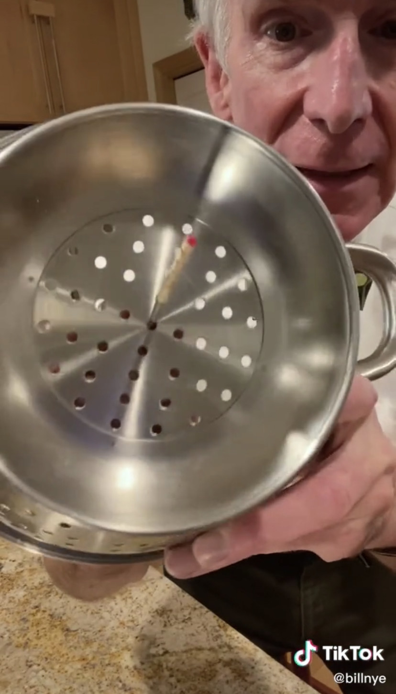 Bill Nye poking a stick through a strainer