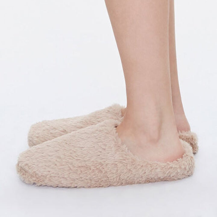 side view of model wearing plush fuzzy slippers in taupe