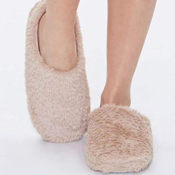 model wearing plush fuzzy slippers in taupe