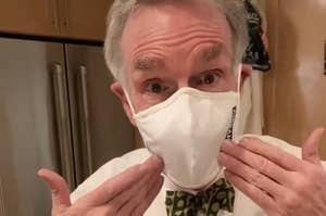Bill Nye wearing a face mask and pointing to his face