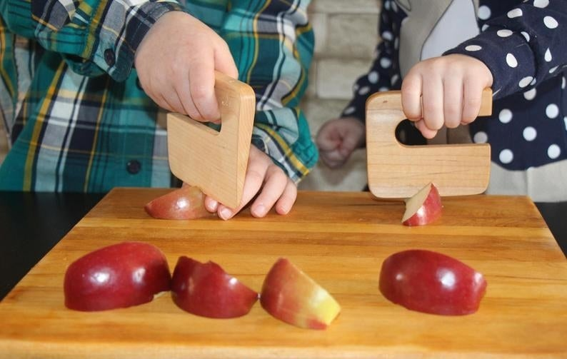 Two child models cutting apple slices with the maple wood chopper with handle