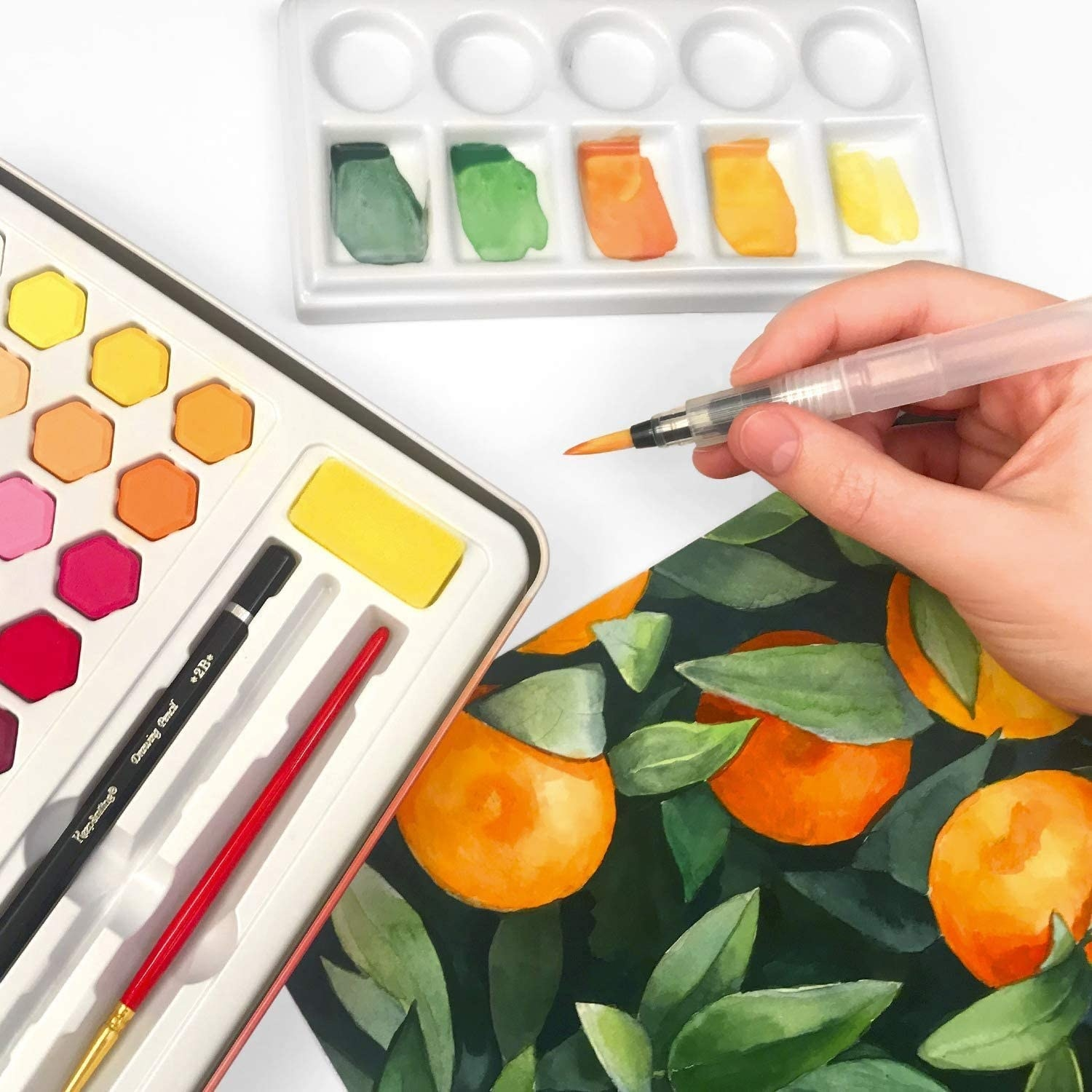 A person using the kit to paint oranges