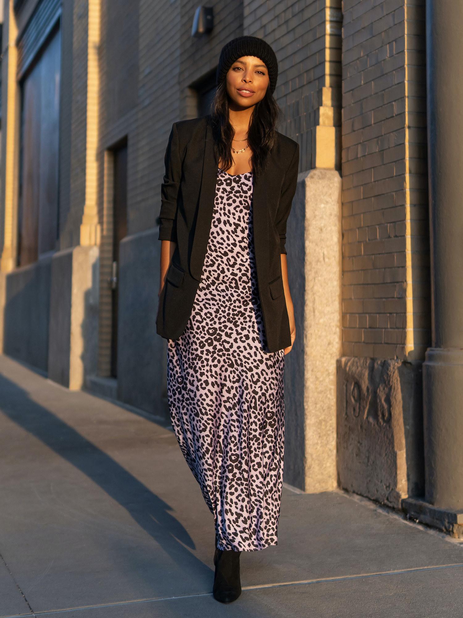 A model posing outside wearing the blazer over a dress
