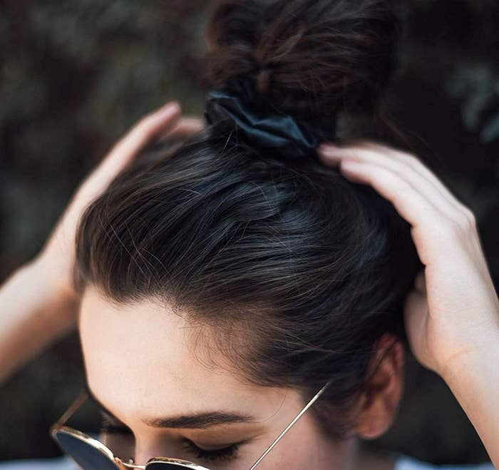 A person wearing sunglasses and a silk scrunchie in their hair