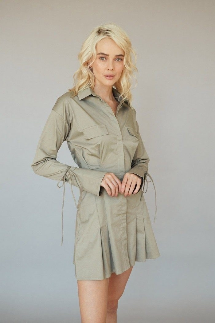 Model wearing the mid-thigh length shirt dress with pleated skirt, ties around the wrist, and pockets on the chest in olive green