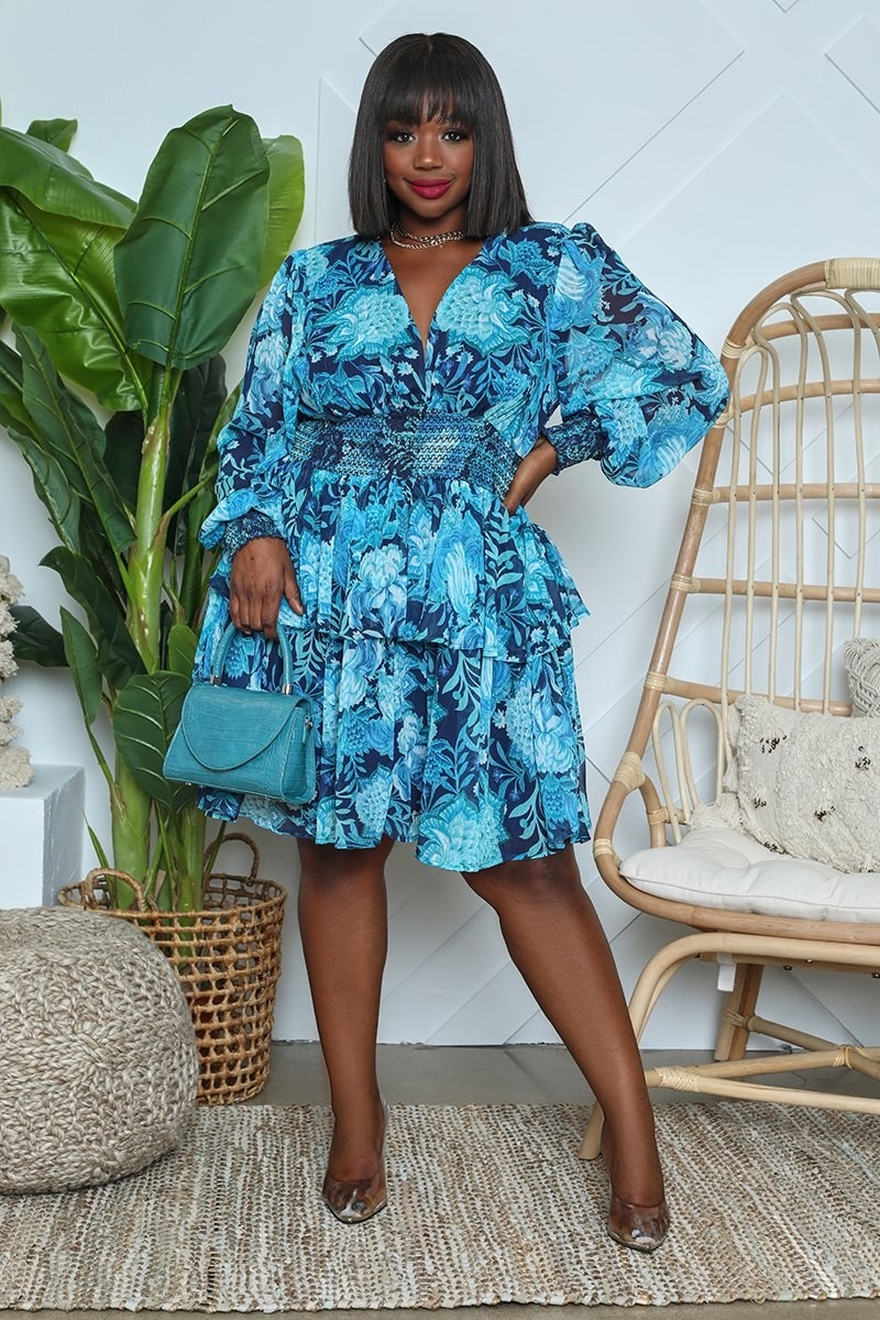 Model wearing the ruffled knee-length tiered dress in blue with light blue florals all over it