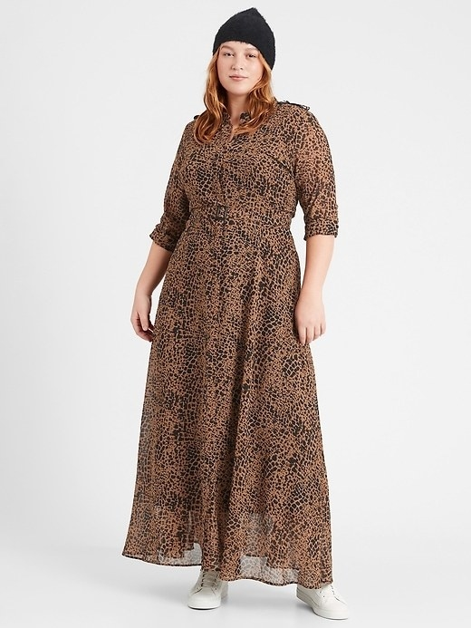 Model wearing the ankle-length button front dress in a tan and black dotted print