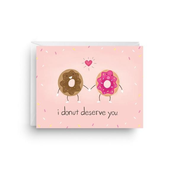 """A pink background with sprinkle print, and two anthropomorphic donuts hold hands, with """"I donut deserve you"""" written below"""