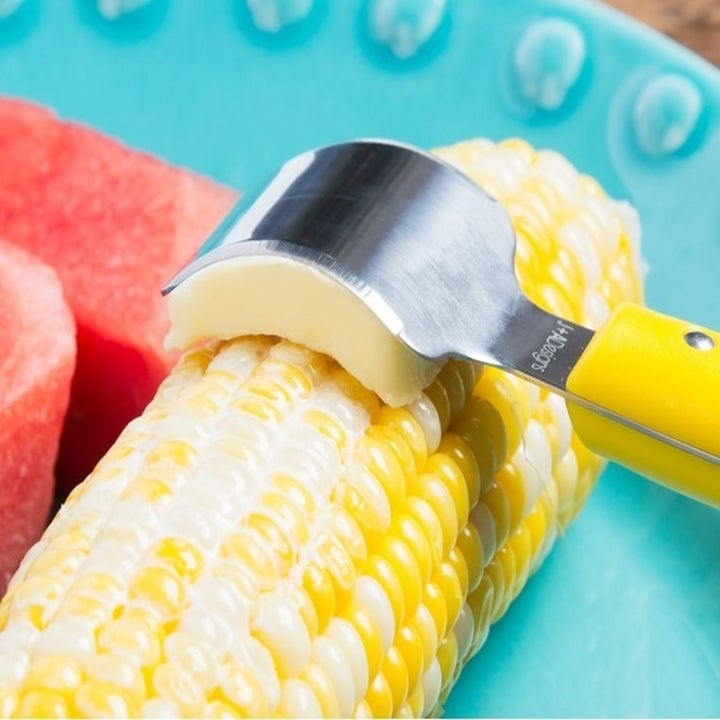 The curved butter knife gliding a slide of butter along a cob of corn