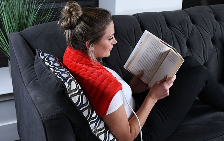 a model sits on a couch with the heating pad draped over their shoulders