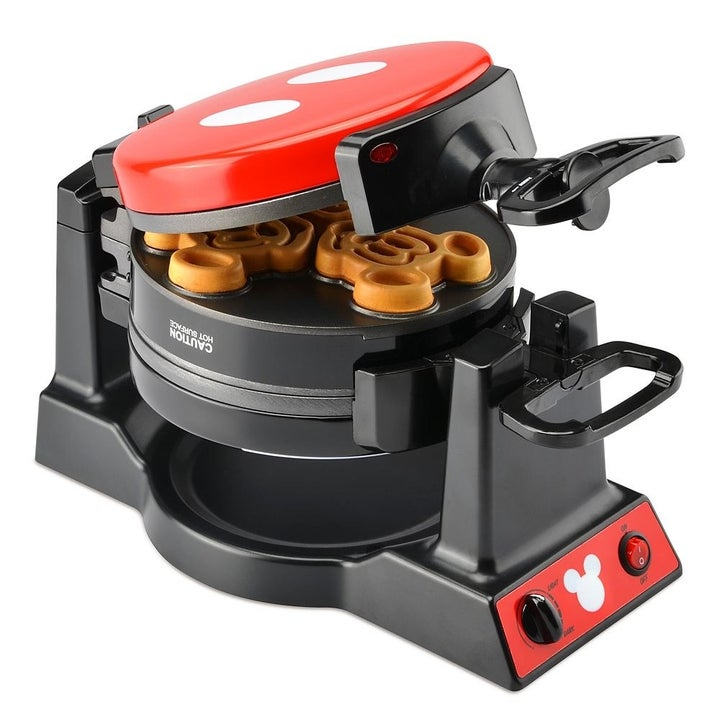 The open waffle maker flipped to show the red pants of Mickey Mouse printed on the top, and three mini waffles shaped like the head of Mickey Mouse inside