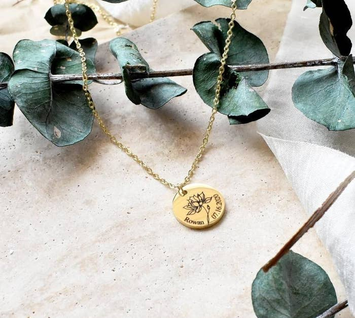 The necklace placed alongside eucalyptus stems