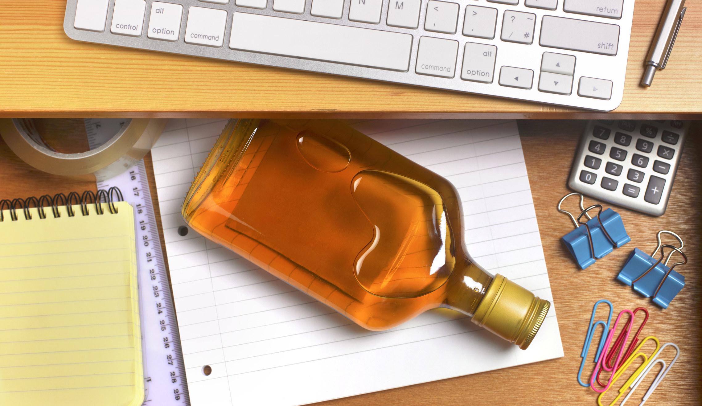 A liquor bottle in a desk drawer