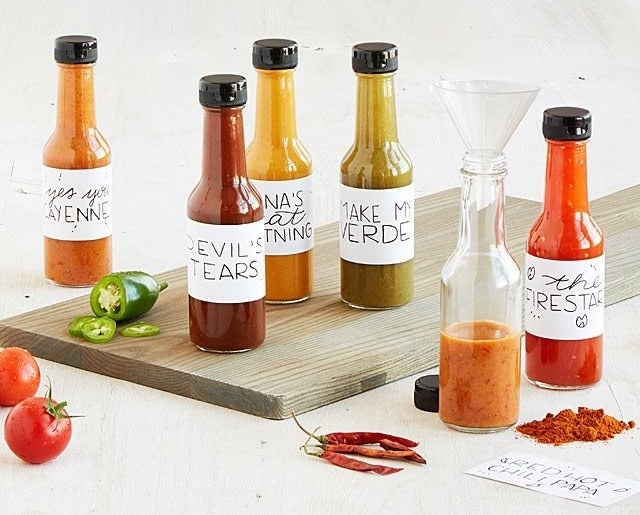 Five bottles of hot sauce with homemade labels and one open bottle partially filled with a funnel at the top surrounded by peppers and other various ingredients