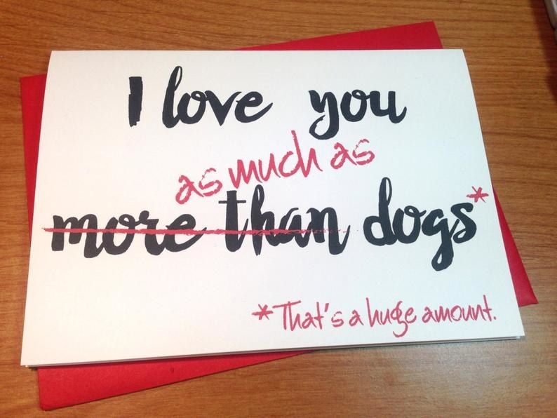 """A white card that says """"I love you more than dogs"""" in black, with """"more than"""" crossed out in red, and replaced with """"as much as (that's a huge amount"""""""