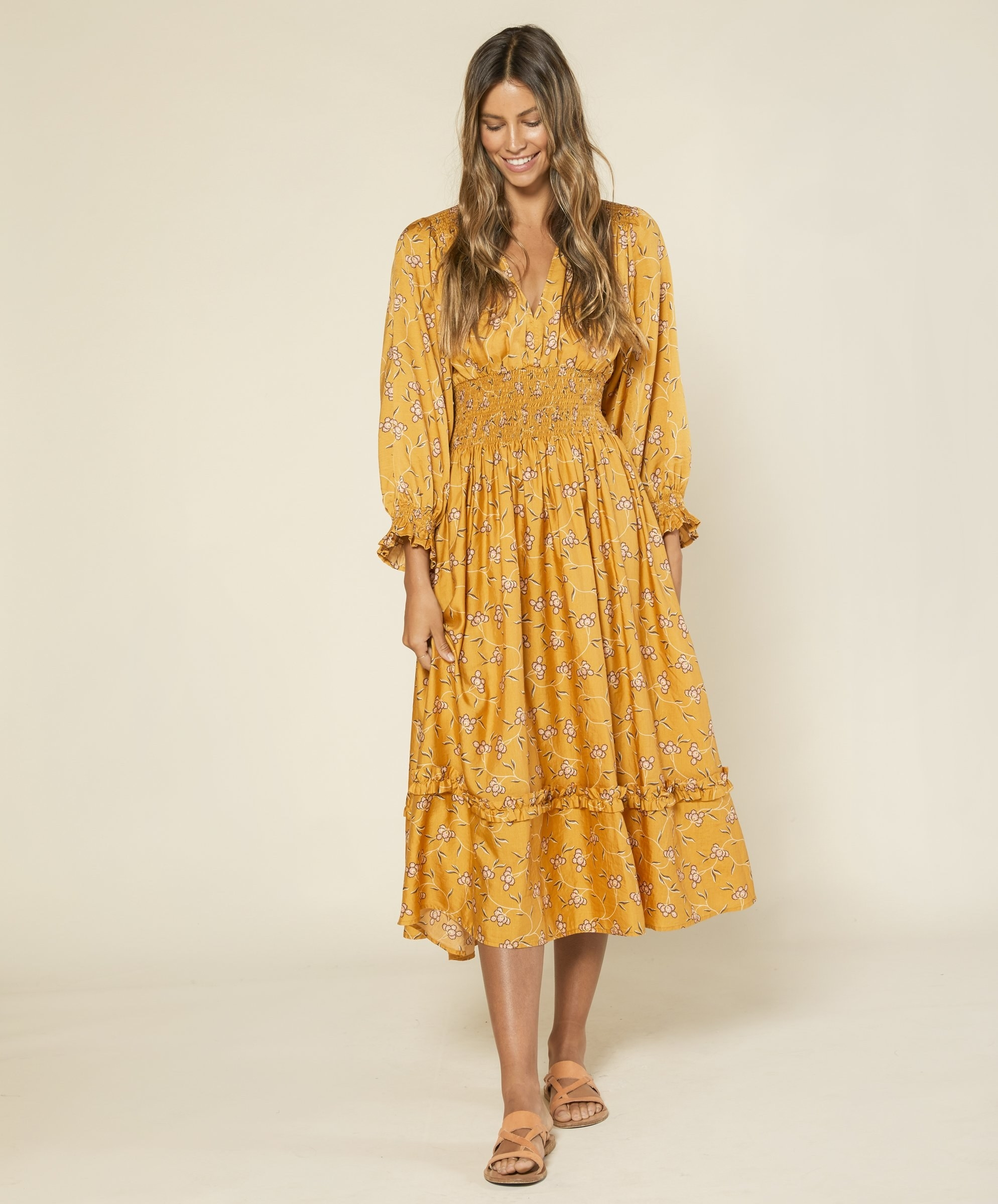 Model wearing the mid-calf length dress with elastic smocking at waist, shoulder, and sleeves in yellow with small white flowers on it
