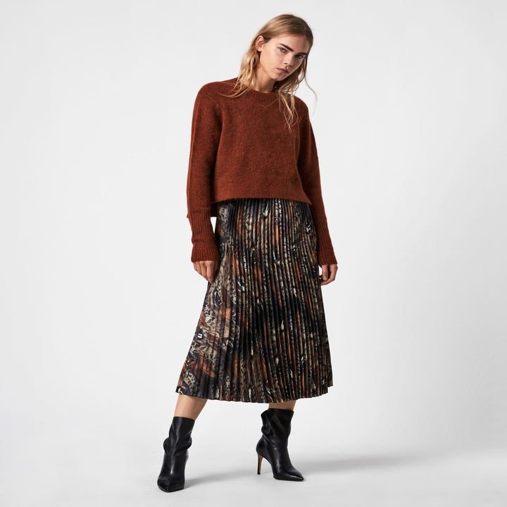 Model wearing the pleated slip dress and brown sweater over it