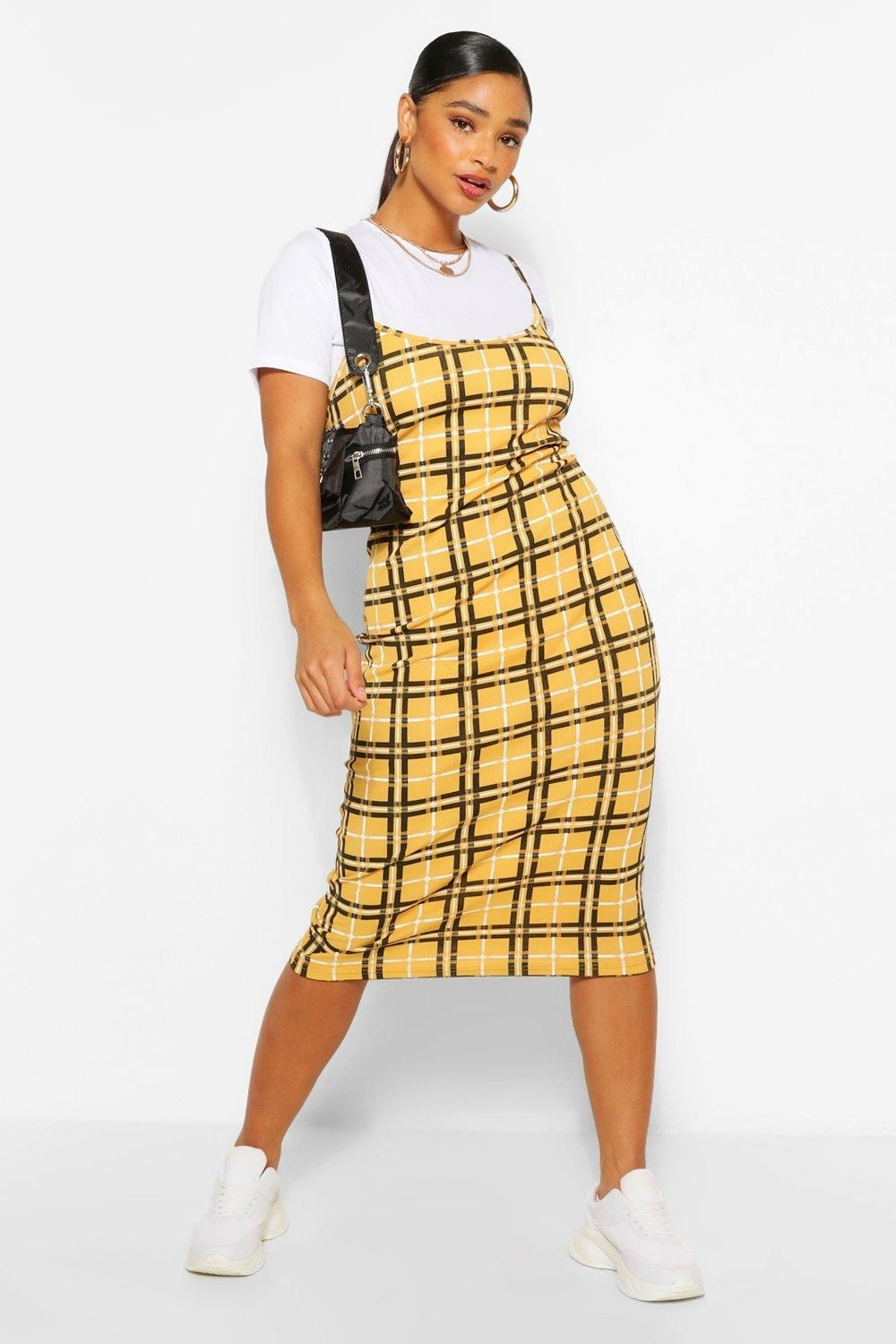Model wearing the knee-length spaghetti strap dress in yellow with black and white plaid and a white short-sleeved t-shirt under it