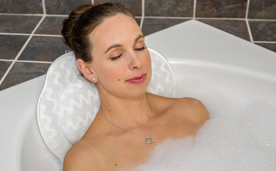 a model sits against the bath pillow in a bubble bath,
