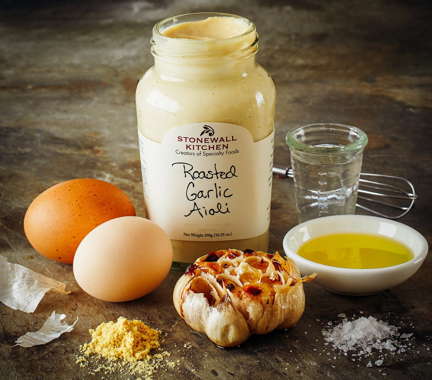 A jar of Stonewall Kitchen roasted garlic aioli surrounded by fresh garlic cloves, eggs, and oil on a countertop