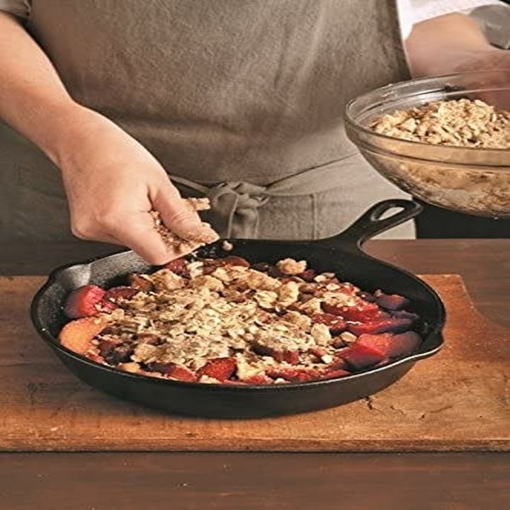 A model spreading crumbs over top a baked dish in a cast iron skillet