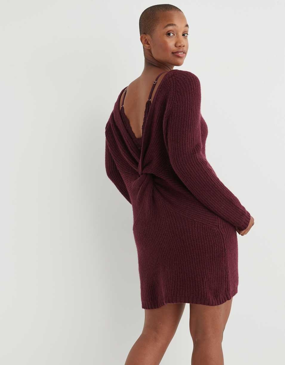 Model showing the back of the dress with the deep v and twist in the middle in burgandy