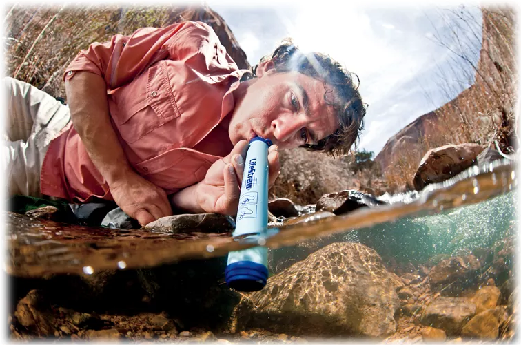Camper uses blue water filtration device to safely drink water from a stream