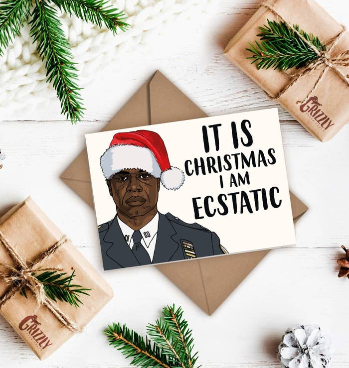 """A card with a straight-faced Holt in a Santa hat that says """"It is Christmas I am ecstatic."""""""