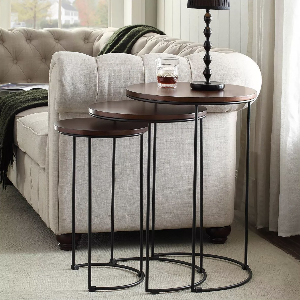A set of three circular nesting tables with wooden top and metal legs