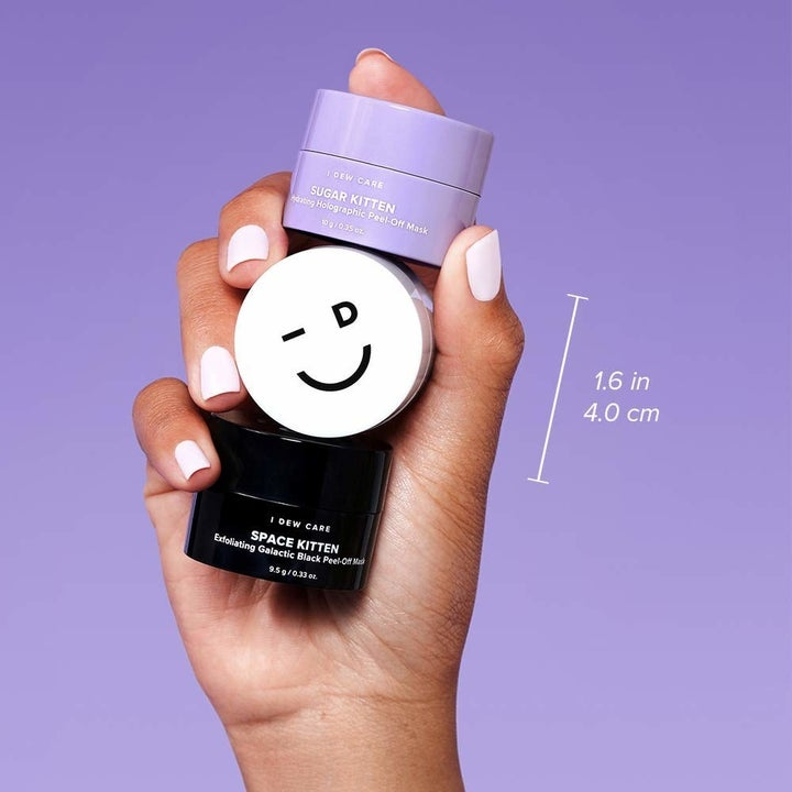 hand holding the purple, white, and black mini masks