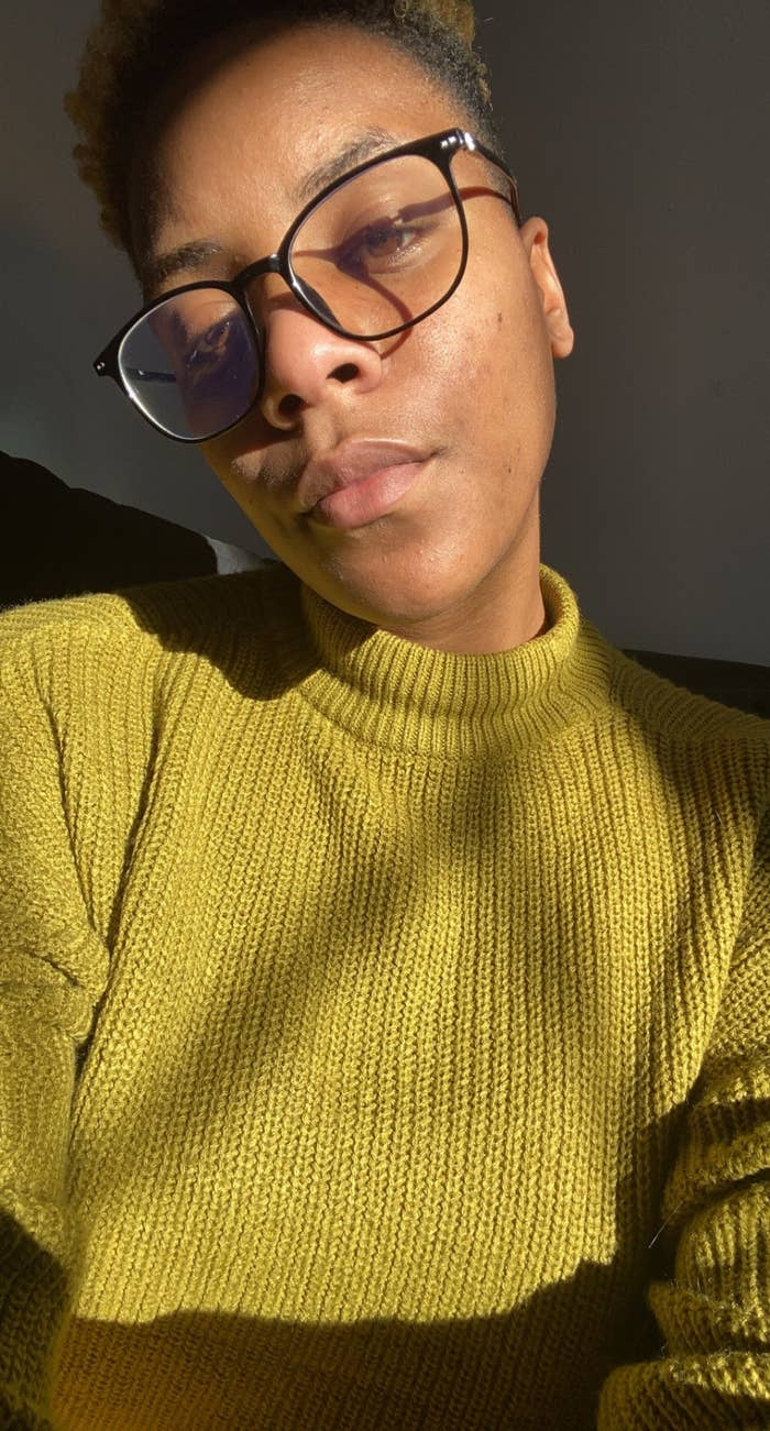 An African-American woman with short hair and glasses is looking at the camera as the light from the sun hits her face.