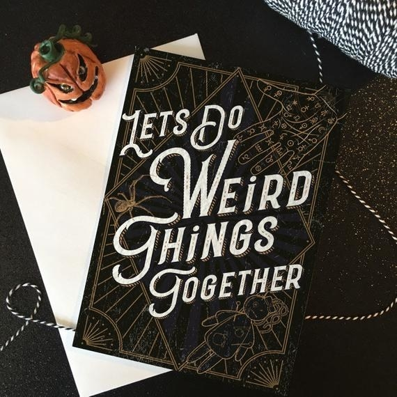 """A black card with gold etchings of a voodoo doll and a palmistry hand, and the words """"Let's do weird things together"""" in white"""