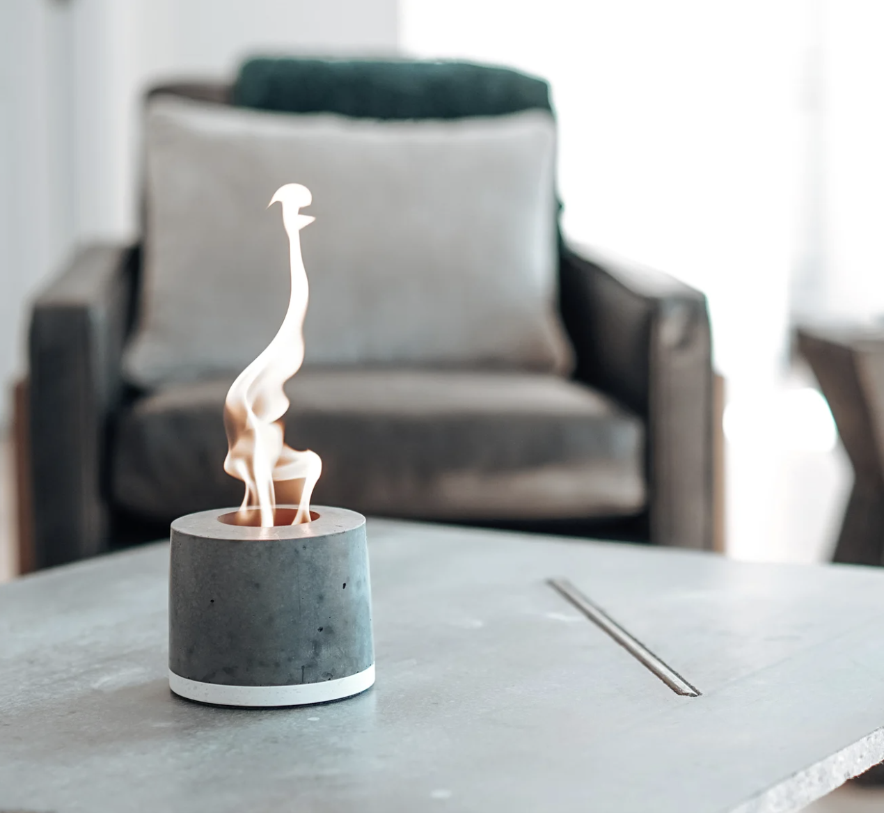 a concrete fireplace with a tiny flame