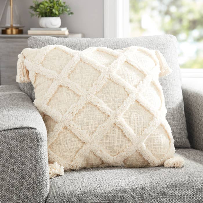 A cream pillow on a grey couch