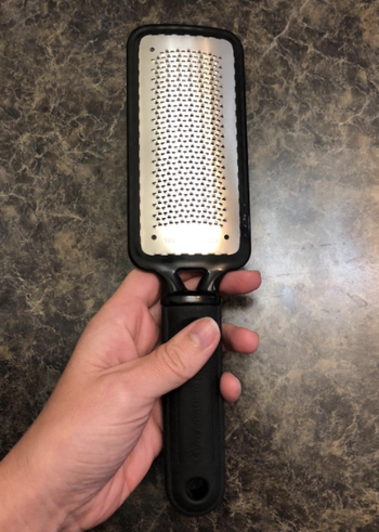 Reviewer holding foot scraper in hand