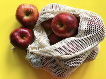 A large reusable produce bag filled with apples