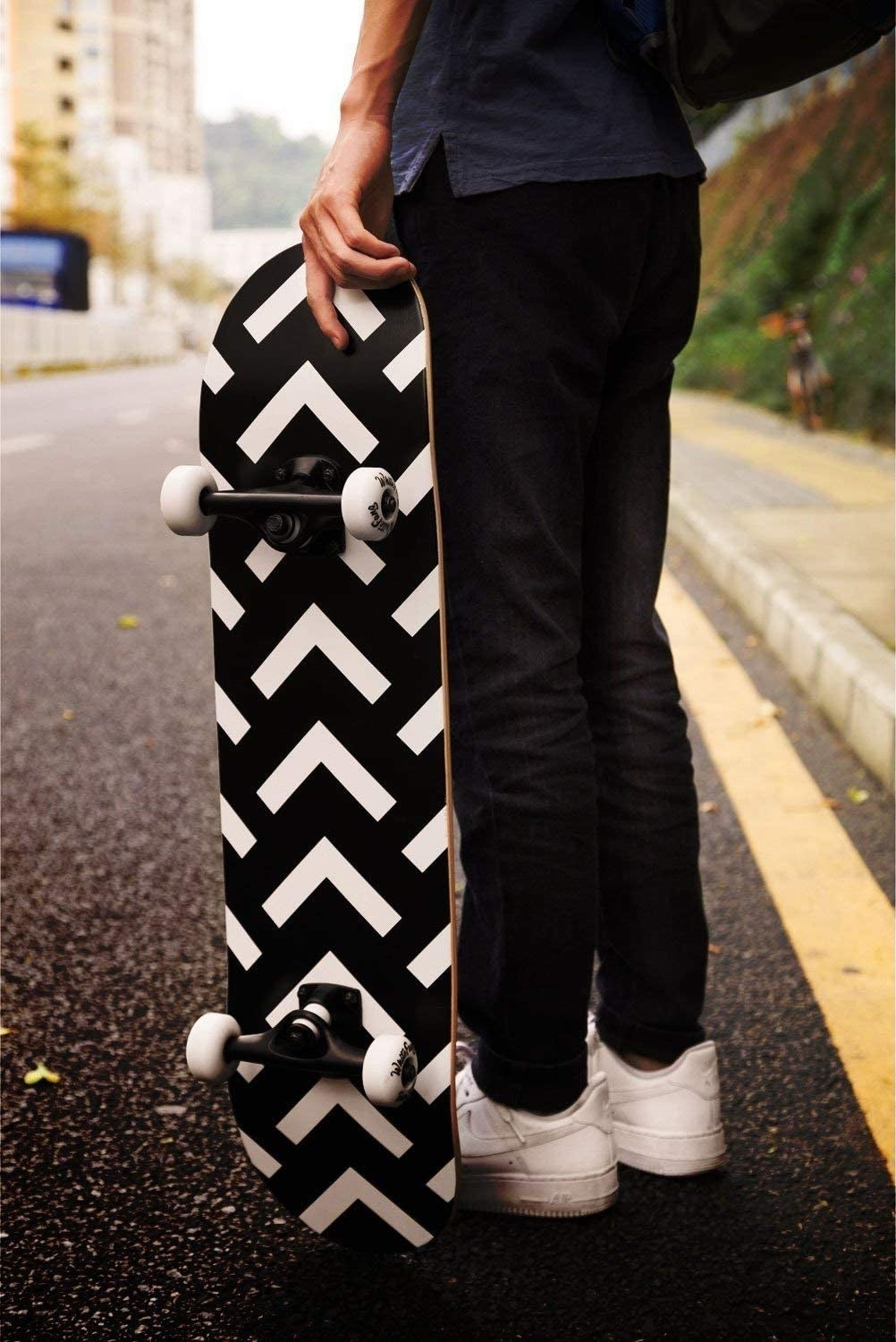 Model holding a black skateboard with black and white v-pattern on the back and two sets of white wheels