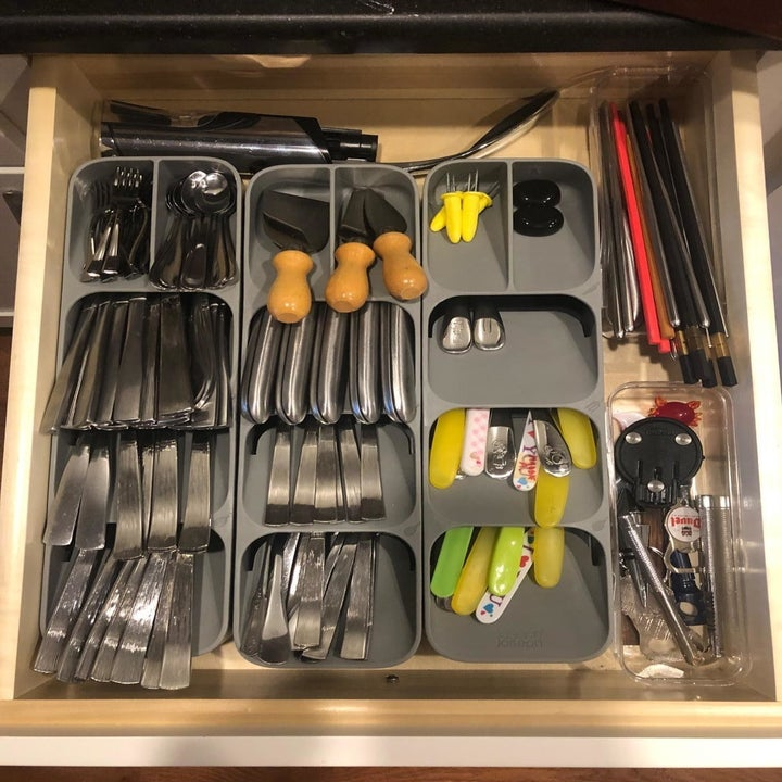 A reviewer photo of an open drawer filled with three drawer organizers sitting side-by-side and filled with an array of different utensils